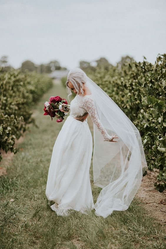a chic A line wedding gown with a lace bodice and long sleeves, an open back and a plain skirt