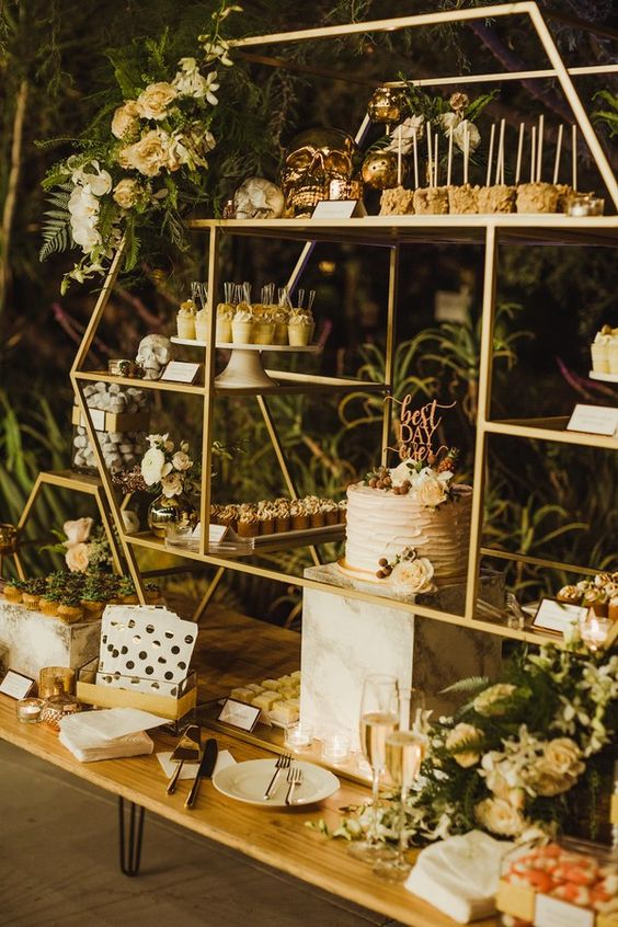 a chic dessert table of gold metal constructions with glass shelves and neutral blooms and greenery