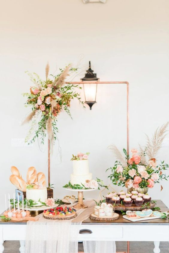 a chic fall dessert table with a copper frame decorated with pastel blooms, greenery and pampas grass