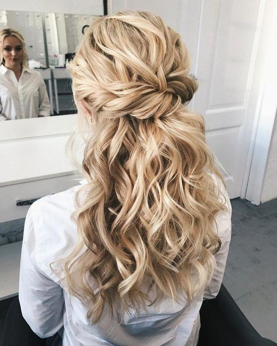 a chic wedding hairstyle with a twisted voluminous top, twisted braids and waves down is great for long hair