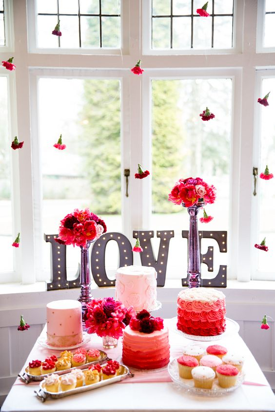 a colorful dessert table with pink and red blooms, flowers hanging over the table and bright sweets