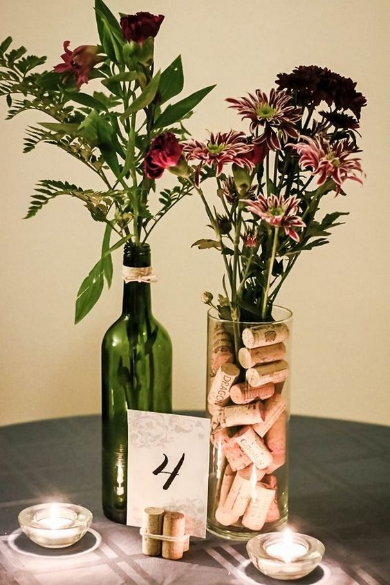 a cool vineyard wedding centerpiece of a wine bottle with blooms and a tall vase with corks and blooms plus candles
