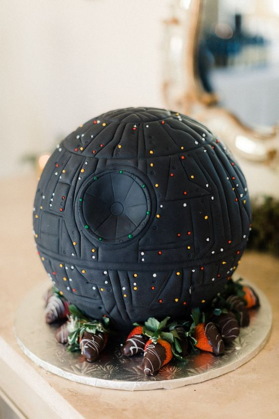 a creative wedding cake shaped as a Death Star and served with fresh starwberries in chocolate is a great wedding dessert