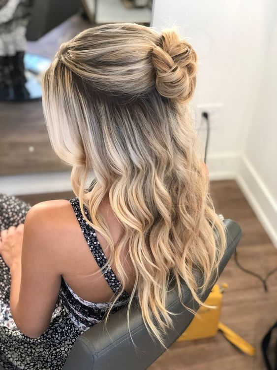 a cute wedding half updo with a volume on top, a top bun and waves down including those framing the face