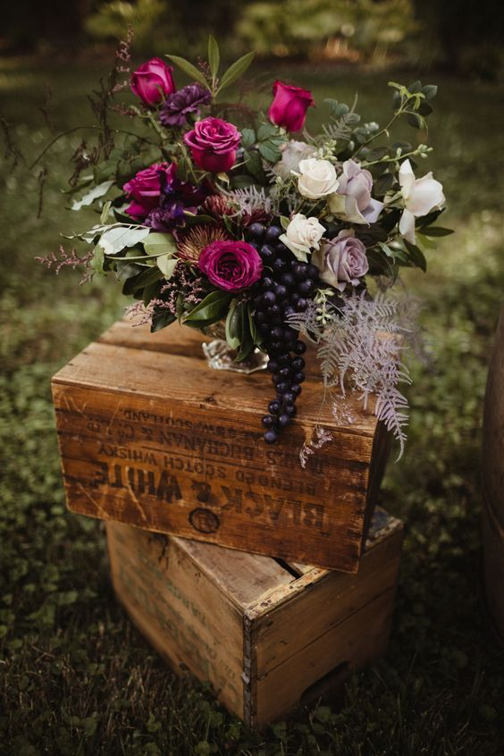 a fall vineyard wedding centerpiece of a silver vase, fuchsia, lilac and white blooms, greenery and grapes