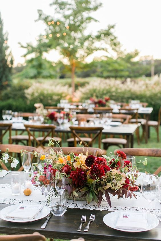 a fall vineyard wedding centerpiece of burgundy, red and marigold blooms and greenery looks fantastic
