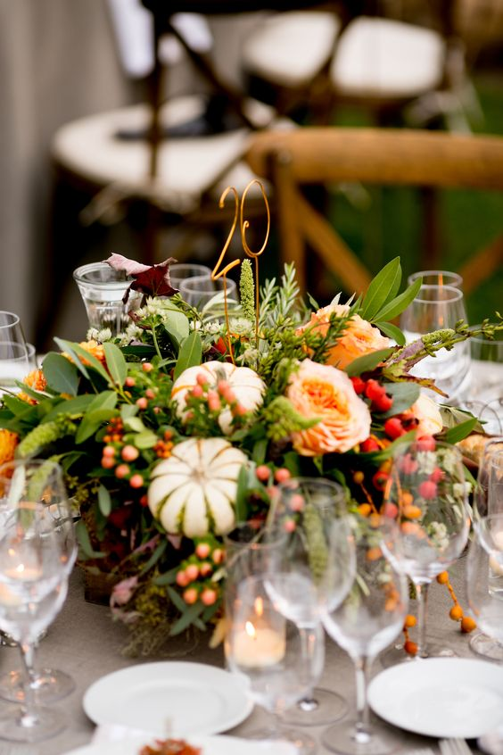 a fall vineyard wedding centerpiece of greenery, bright blooms, berries and mini pumpkins plus a wire table number