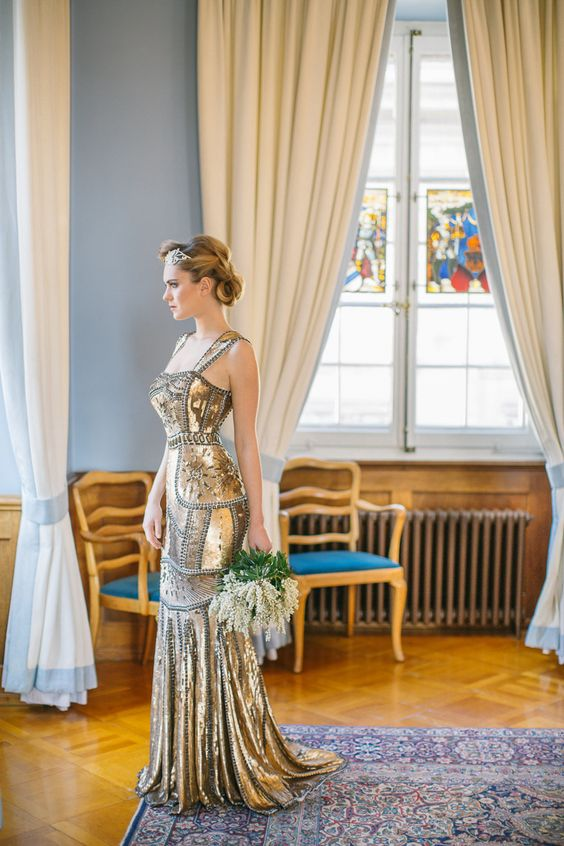 a fantastic art deco inspired wedding dress with a fitting silhouette, wide straps, a small train and rhinestones
