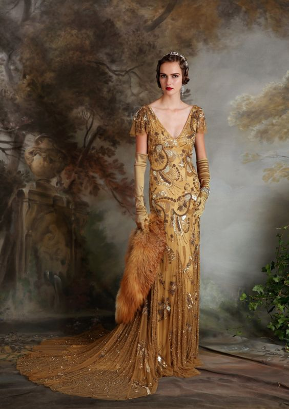 a fantastic gold wedding dress with embellished patterns, cap sleeves and a deep neckline plus an embellished train