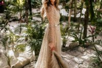 a fully embellished gold wedding dress with illusion sleeves, a deep V-neckline and a train