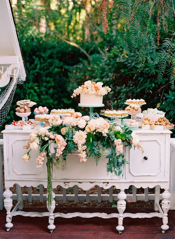 a garden wedding dessert table - a vintage whiet cupboard with greenery and pink flowers and blush sweets