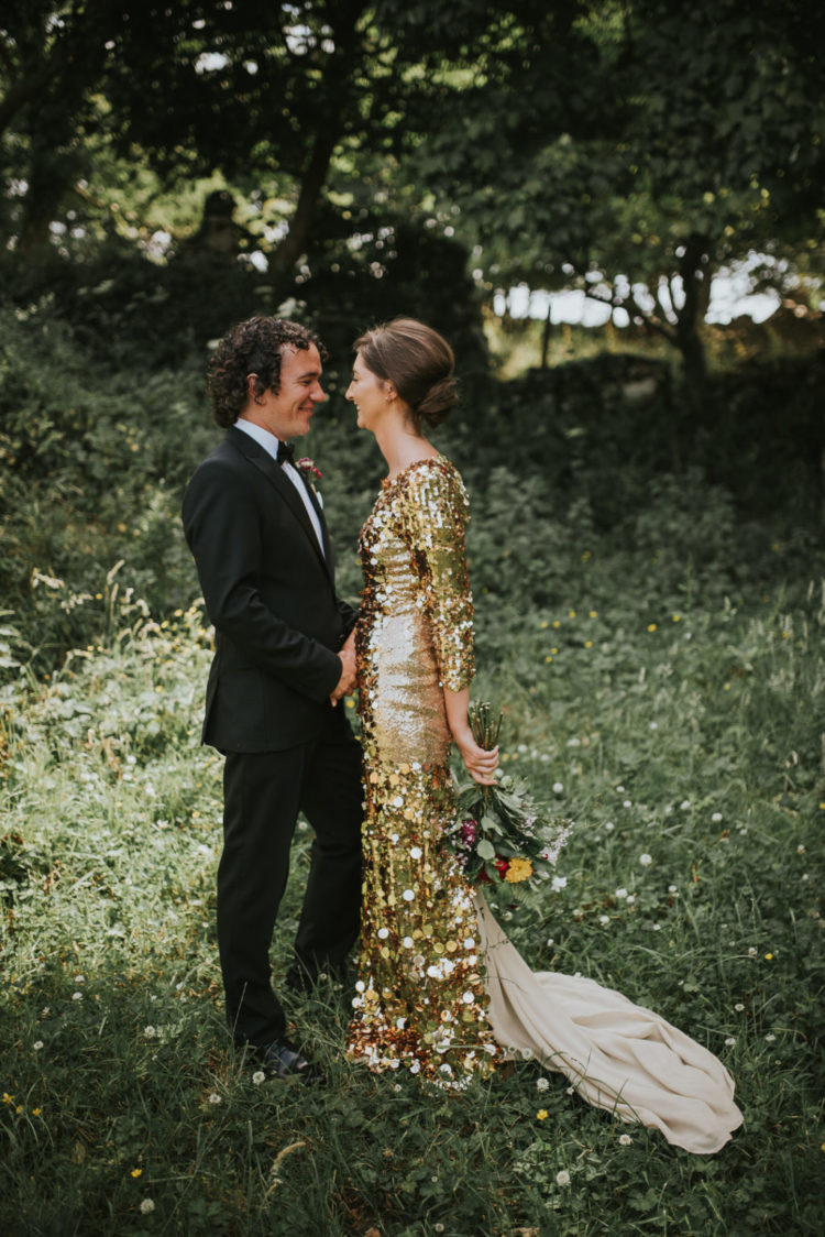 a gold large sequin sheath wedding dress with long sleeves, a high neckline and a tan sheer train just wows