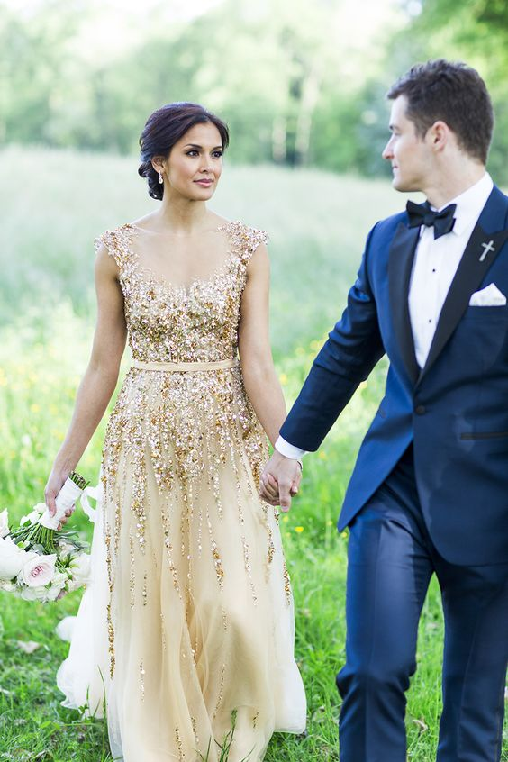 a gold wedding dress with An A line silhouette, an embellished bodice, an illusion neckline and a partly embellished skirt
