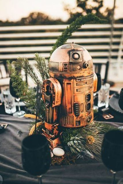 a gorgeous Star Wars wedding centerpiece of greenery, succulents and an R2D2 is amazing for your themed wedding