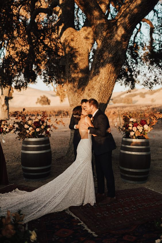 a gorgeous vineyard fall wedding ceremony space with a living tree, barrels with bold floral arrangements, bold printed boho rugs