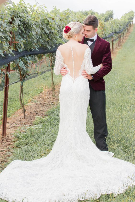 a lace mermaid wedding dress with long sleeves, an illusion back on buttons and a long train is refined