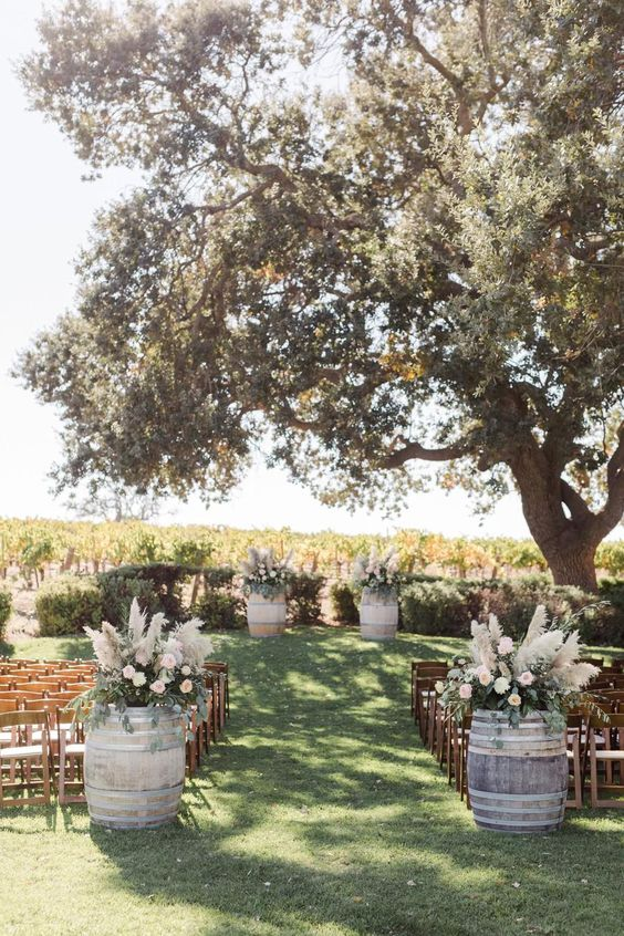 a lovely fall wedding ceremony space with a living tree, barrels with neutral blooms and pampas grass, simple chairs
