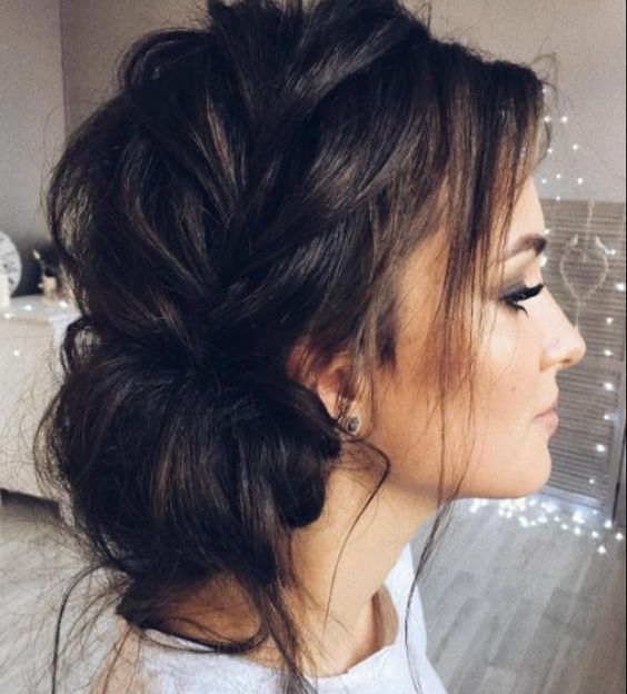 a messy braided low chignon with locks hanging down is a cool and relaxed idea
