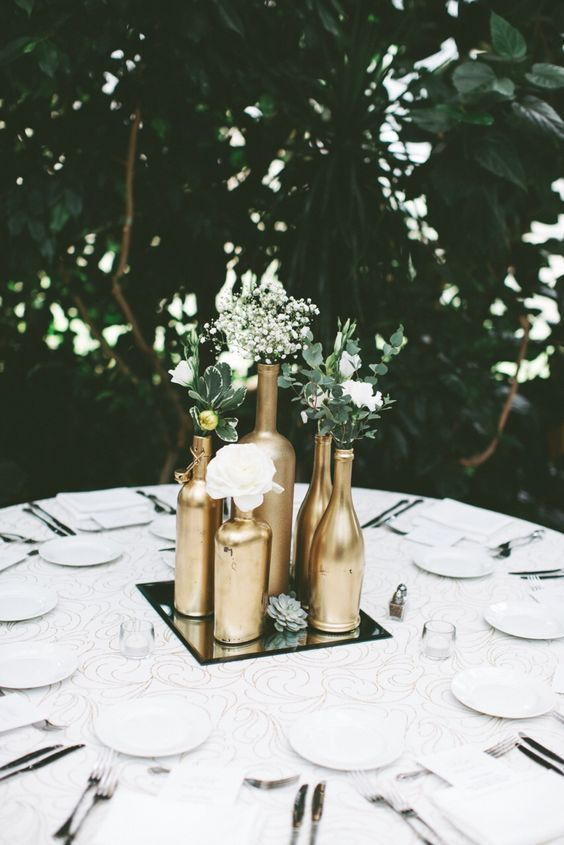 a mirror tray with gold bottles, white blooms, greenery and a succulent is a nice centerpiece for many weddings