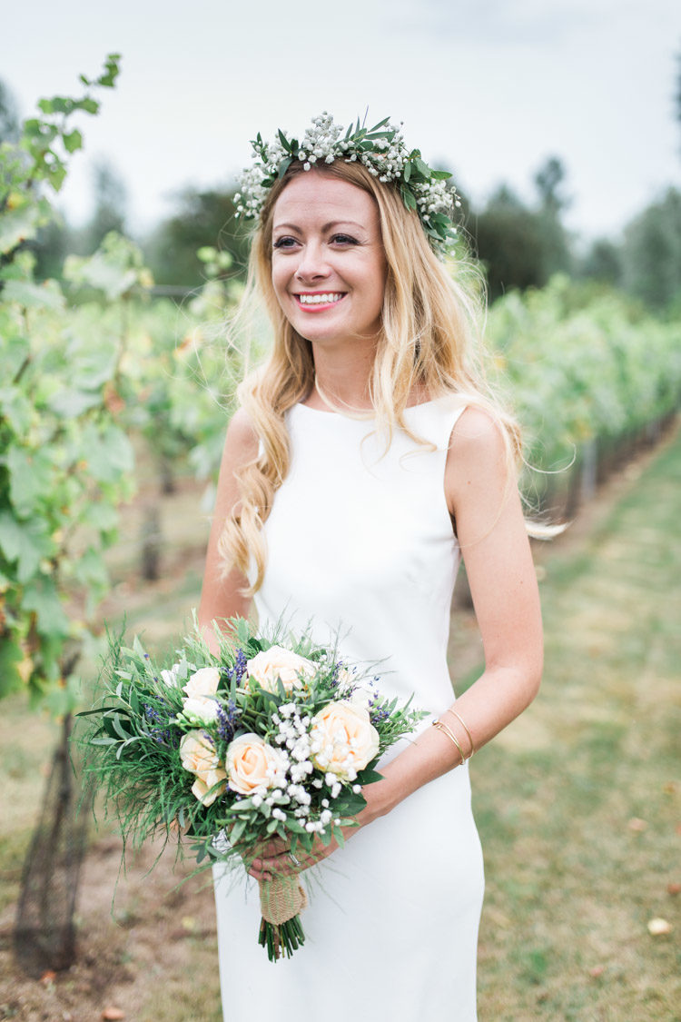 a modern plain sheath wedding dress with no sleeves, a high neckline and a cutout back is a stylish idea