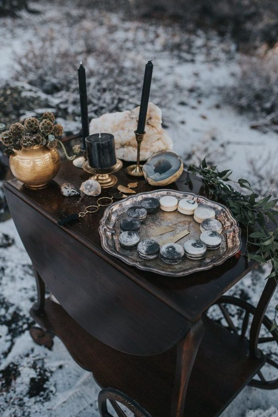 a moody sweets table with dried flowers, black candles, geodes and greenery plus a plate with macarons