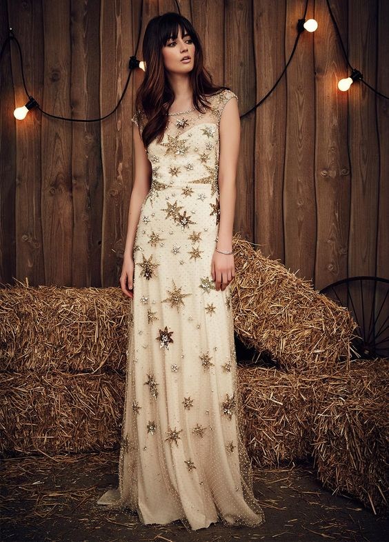 a neutral wedding dress with embellished and shiny gold stars, no sleeves and an illusion neckline for a celestial bride