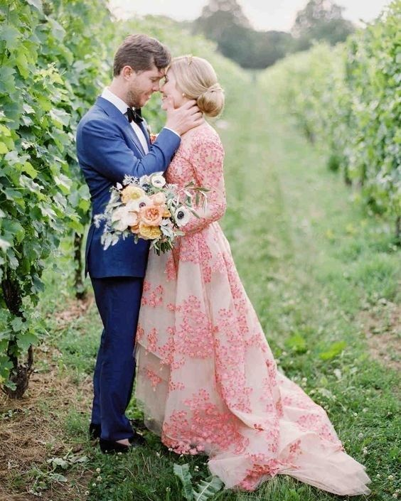 a pink A line wedding dress with a high neckline, long sleeves, bright pink floral embroidery and a train