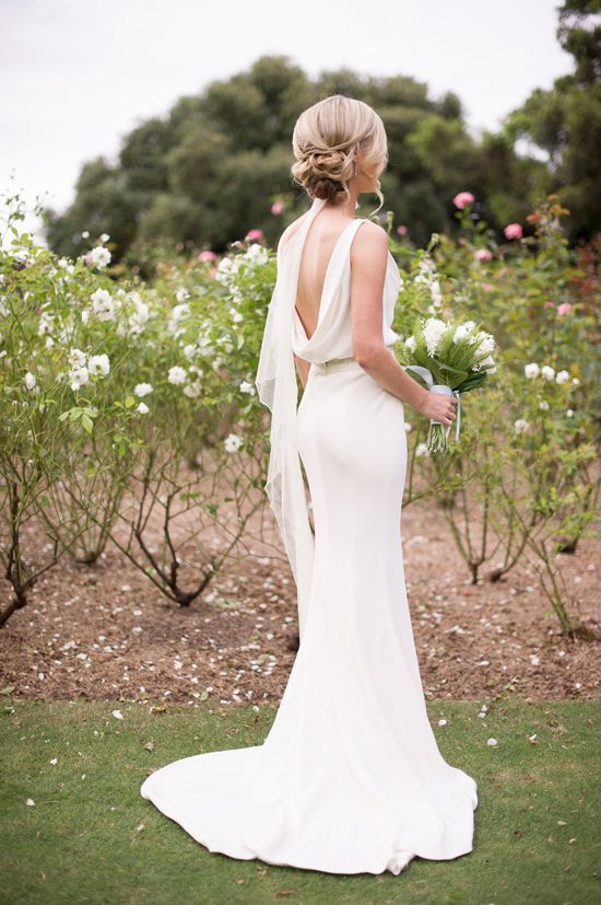 a plain sheath wedding dress with a cowl back, a sash, a train and a veil for a chic and romantic look