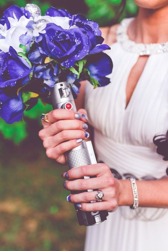 a purple and white wedding bouquet with a Jedi lightsaber holder for a Star Wars bride