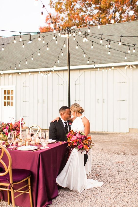 a refined and bold vineyard fall wedding reception with much purple, bold and lush florals and greenery, elegant candles