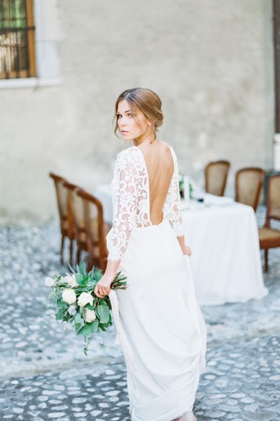 a romantic A line wedding dress with a lace bodice, long sleeves, a cutout back and a plain skirt