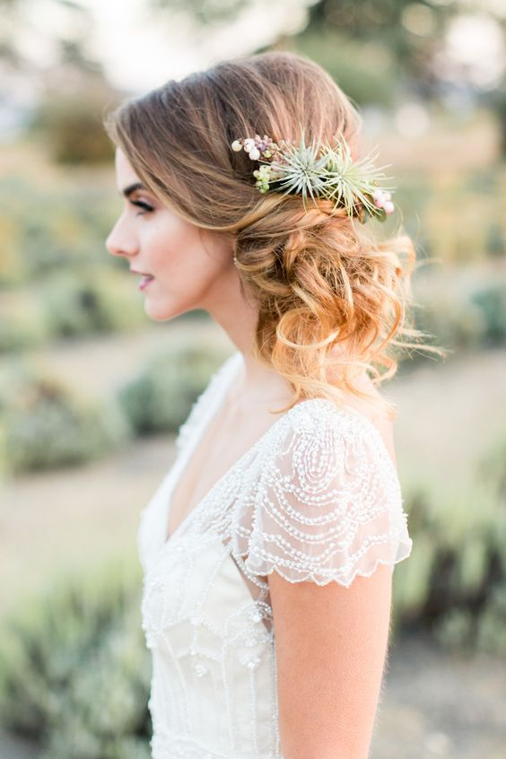 a romantic and wavy side updo with a volume on top and an air plant and berry hairpiece for an accent