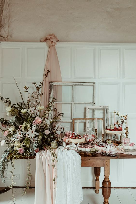 a romantic blush and white dessert table with table runners, a textural greenery and flower arrangement and fresh sweets