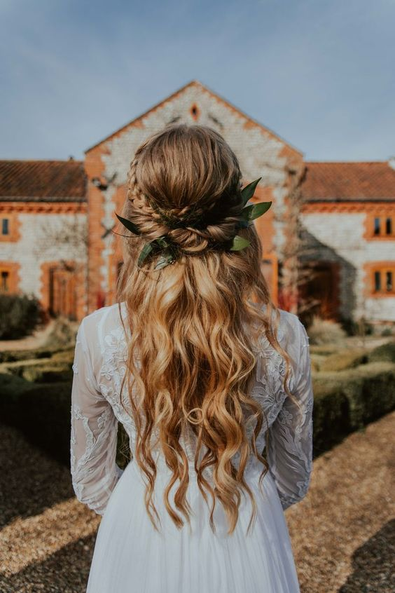 a romantic boho wedding hairstyle with a twisted and braided halo with a volume on top and waves plus leaves