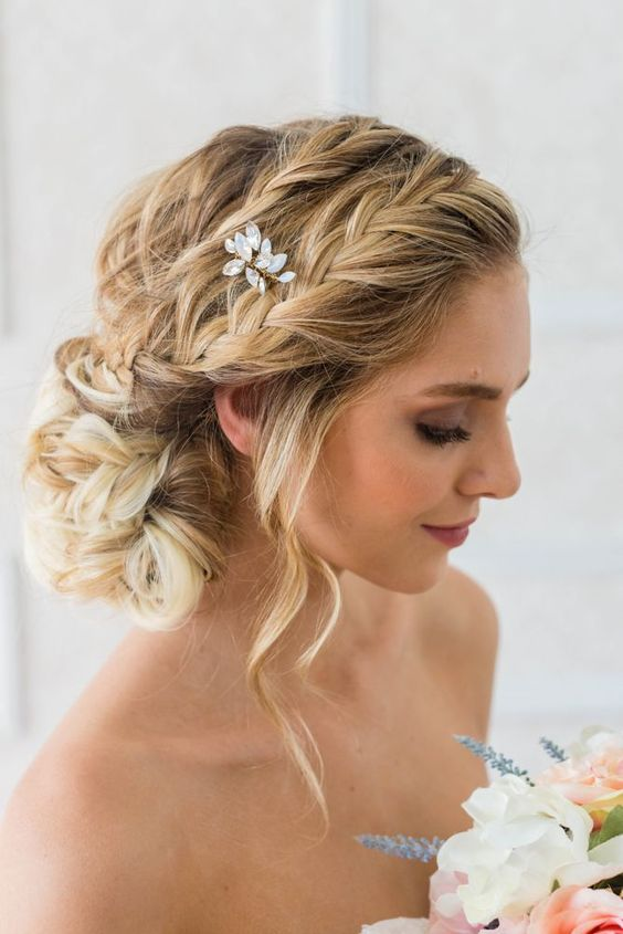 a romantic braided side chignong with several braids on top, some waves down and a crystal hairpiece
