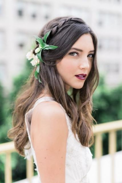 a romantic half updo with a braided halo, a wavy front, a large fresh flower hairpiece and waves down