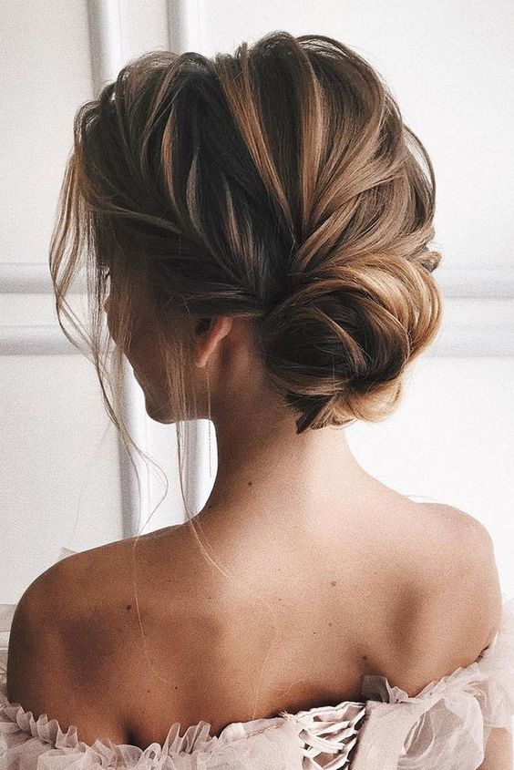 a romantic twisted low bun with much volume and texture on top plus some locks down is elegant