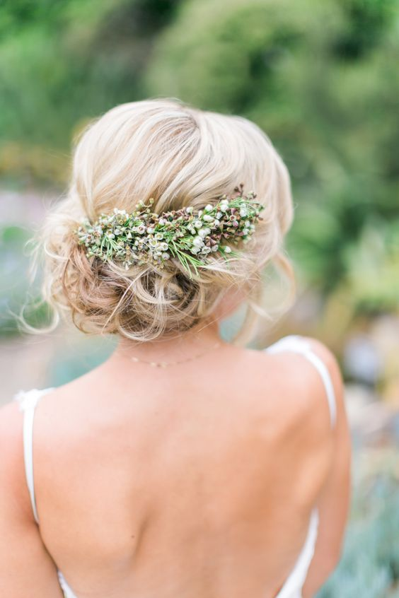 a romantic wavy side updo with a volume on top and a fresh flower and greenery hairpiece for a natural feel