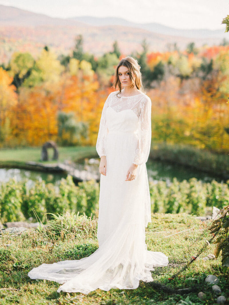 a romantic wedding dress with a lace overdress with long sleeves and a train with a vintage feel