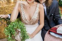 a romantic wedidng dress with a gold sequin bodice, no sleeves, a depe V-neckline and a neutral skirt just wows