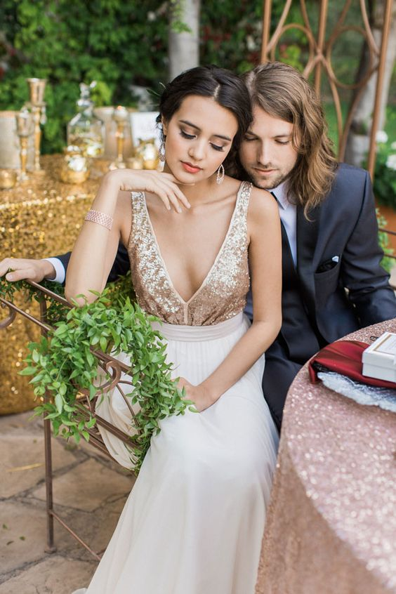 a romantic wedidng dress with a gold sequin bodice, no sleeves, a depe V neckline and a neutral skirt just wows