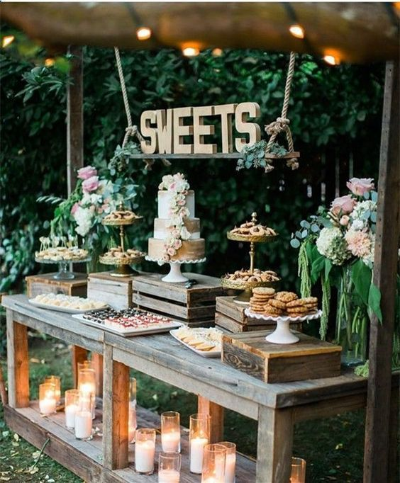 a rustic dessert table made of weathered wood, with crates and boxes, with wooden letters on ropes and lots of candles
