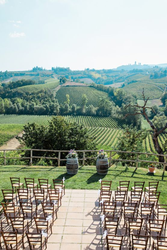 a simple and beautiful vineyard wedding ceremony space with a view od the vines, barrels with floral arrangements