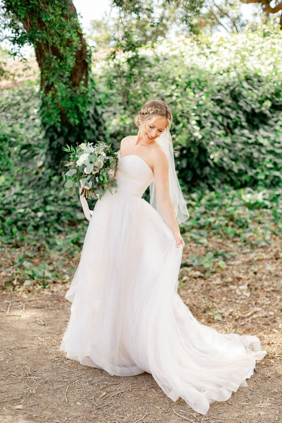 a strapless wedding ballgown with a layered skirt with a train and a veil for a vineyard princess