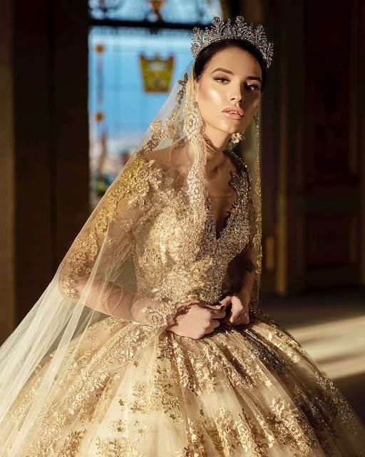 a stunning gold wedding ballgown with intricate gold lace all over the dress, with illusion sleeves, a matching veil and a crown