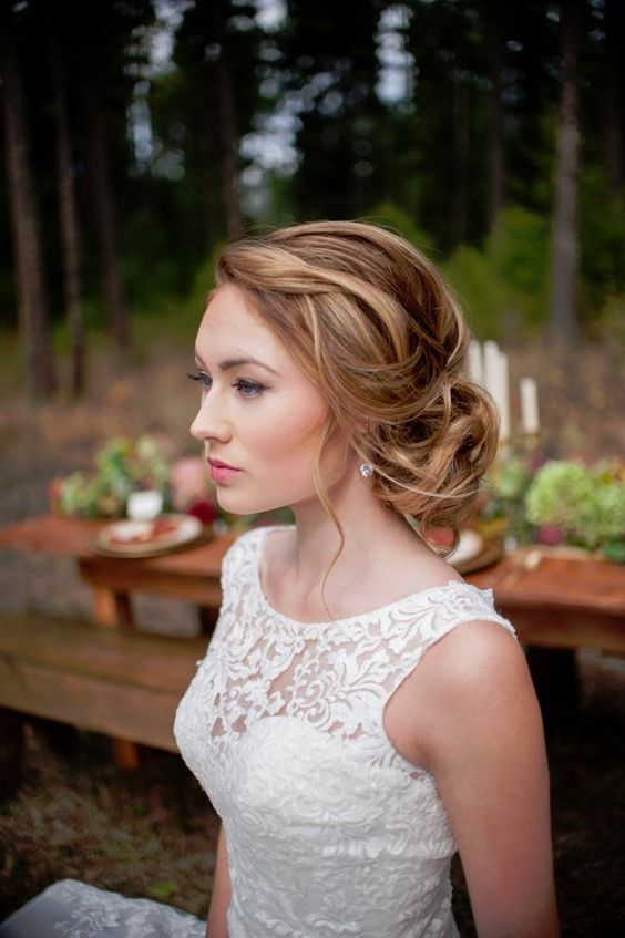 a stylish messy twisted low bun with a messy textural top and somw waves down is a cool idea of a wedding hairstyle