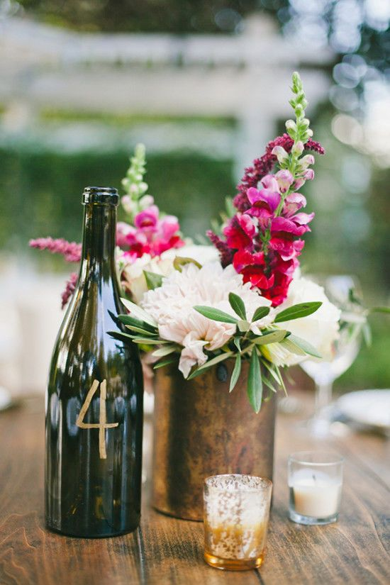 a tin vase with fuchsia and white blooms, a wine bottle as a table number and some candles for a centerpiece