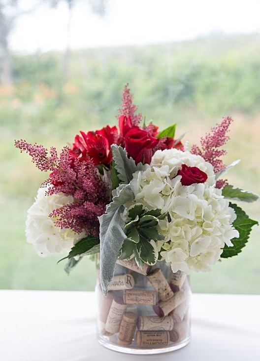 a vase with wine corks, white and red blooms and leaves for a bright summer or fall vineyard wedding