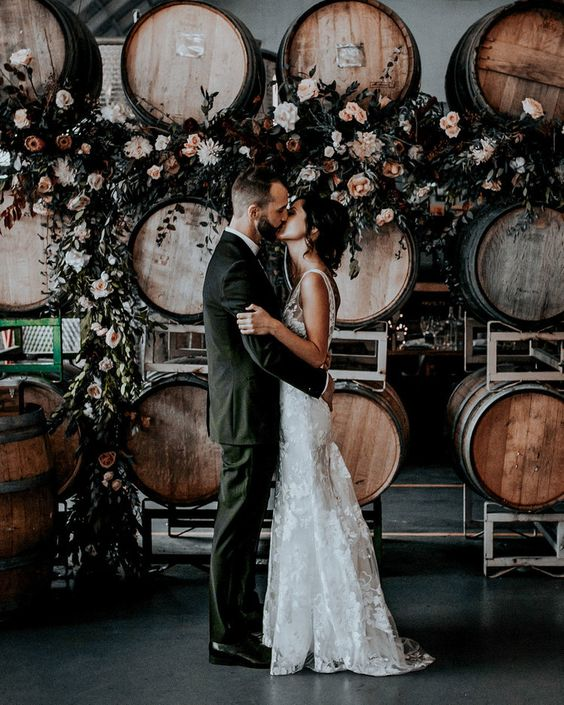 a vineyard wedding backdrop of barrels decorated with greenery, neutral and pastel pink blooms is a creative idea