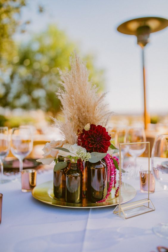 a vineyard wedding centerpiece of a gold trey, apothecary bottles, blush and burgundy blooms, greenery and pampas grass